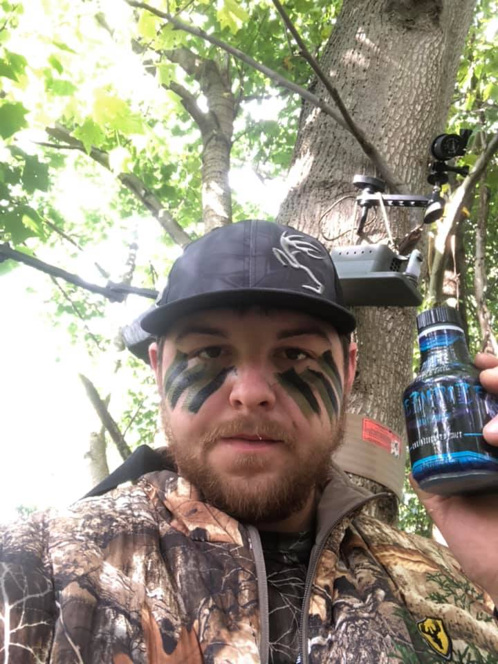 John Richards, Field Staffer in his tree stand with his bow, #1 Hunting Scent Dispenser and Pure Whitetail Mesmerize scent.
