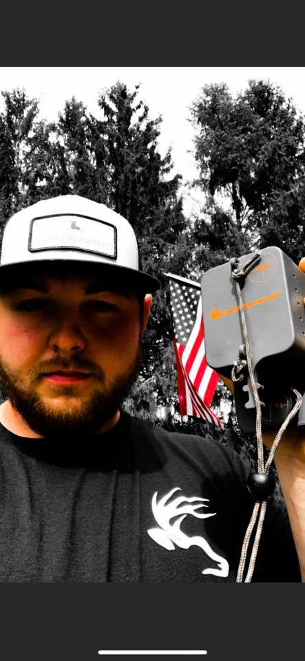 John Richards, Field Staffer holding a ScentBlaster. American Flag and forest in the background.